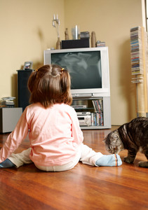 Rear view of little girl sitting on the floor and watching TV with cat near by