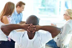 Rear view of relaxed man keeping hands behind head and looking at three employes working