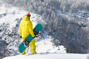 Rear view of snowboarder standing in snowdrift in winter
