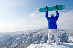 Rear view of sportsman with snowboard standing on top of mount
