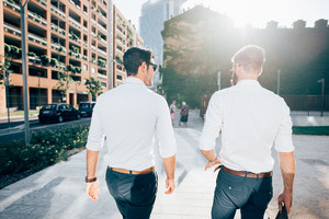 Rear view of two young blonde and black hair modern businessman, walking outdoor in the city  - working, successful, business concept