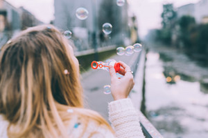 Rear view of young beautiful blonde woman playing with bubble soap, close up on the hand - playful, game, childhood concept