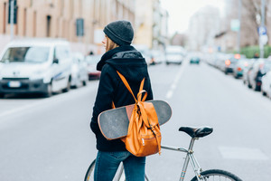 Rear view of young beautiful caucasian woman with backpack, holding bike and skateboard - sportive, athletic concept