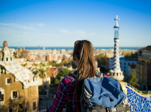 Rear view of young female tourist looking at view in Parc Guell in Barcelona, Spain.