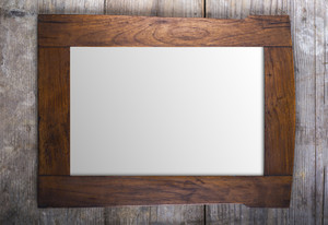 Rectangle picture frame laid on wooden floor backround.