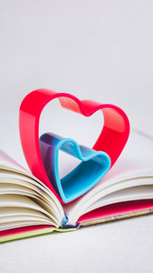 Red and blue hearts over diary book on white table, vertical orientation