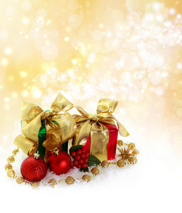 Red and green Christmas gifts over golden lights background