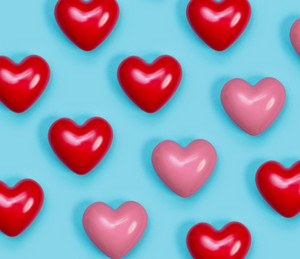 Red and pin shiny hearts on a blue background