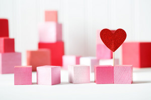 Red and pink wooden blocks with small heart on white background
