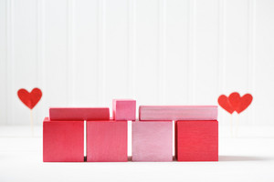 Red and pink wooden blocks with small hearts on white background