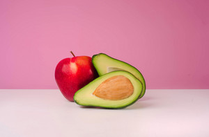 Red apple and sliced avocado isolated on pink background