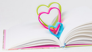 Red blue and green hearts over diary book on white table