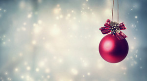 Red Christmas ornament with ribbon in snowy night
