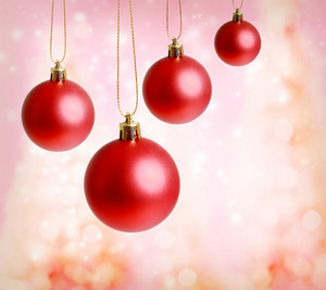Red christmas ornaments with pink lights background