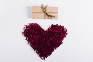 Red decorative heart and a box with a gift on a white background, top view