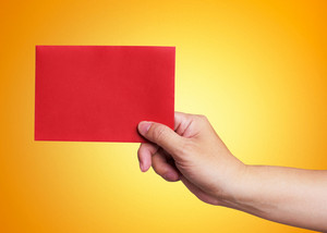 Red envelope in the hand isolated on orange background