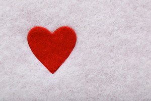 Red felt heart in white felt background