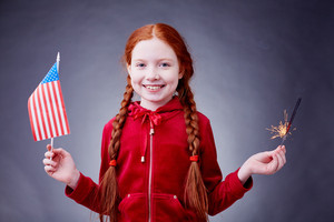 Red-haired girl with American flag and Bengal light