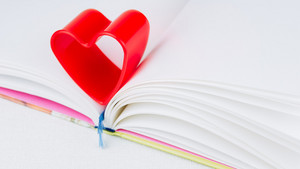 Red heart over diary book on white table