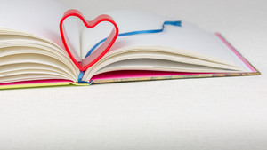 Red heart over diary book with bookmark on white table