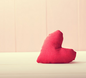Red heart pillow on pink wooden wall