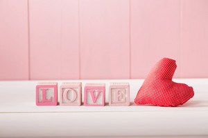 Red romantic textile heart with the word Love in pink letters on wooden alphabet blocks against a rustic wooden pink background with copyspace for your Valentine greeting