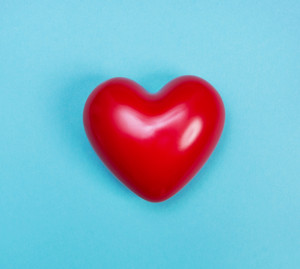 Red shiny heart on a blue background