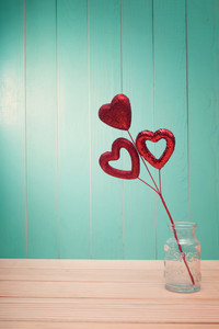 Red shiny heart ornaments on vintage teal wood