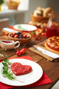 Red wooden heart and green branch on plate with traditional food on background