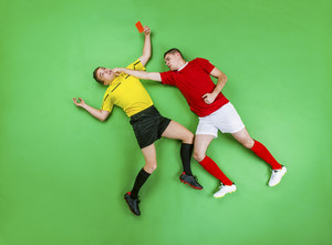 Referee giving red card to a football player. Studio shot on a green background.
