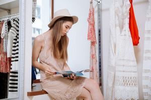 Relaxed attractive young woman in hat sitting and reading magazine in clothing store