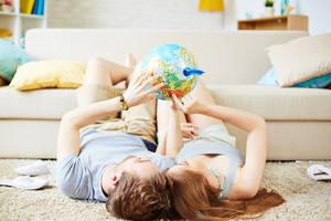Relaxed couple with globe dreaming of summer travel