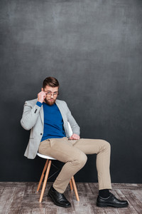 Relaxed young businessman sitting on chair and looking over glasses