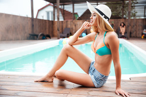 Relaxed young woman in hat and shorts thinking and sitting near swiming pool