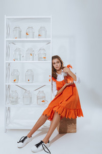 Relaxed young woman sitting and holding glass jar with gold fish