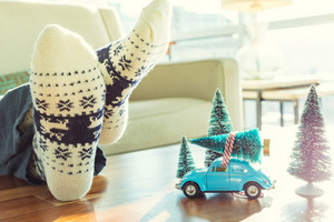 Relaxing man with miniature blue car carrying a Christmas tree on its roof