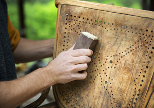 Restoration, removing paint from antique chair with sandpaper