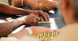 Retired people, seniors and free time. Old latino men having fun and playing game of domino in Cuba.