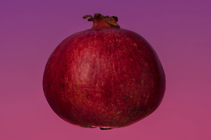 Ripe fresh pomegranate isolated on pink background