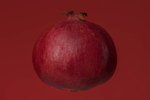 Ripe fresh pomegranate isolated on red background