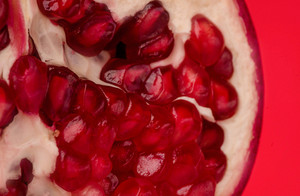 Ripe pomegranate fruit segment isolated on red background