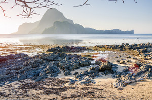 Rocky Beach during low tide in morning light in front of amazing Cadlao Island, El-Nido, Palawan, Philippines