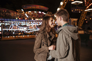 Romantic couple in amusement park. in warm clothes