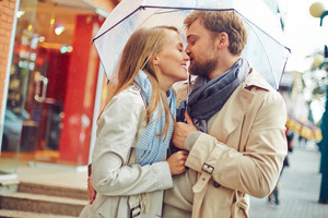 Romantic couple kissing each other during the rain