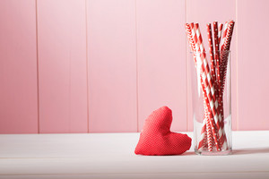 Romantic Valentines Day greeting card design with a handcrafted red heart and glass full of colorful red and white straws against a rustic pink wooden wall with copyspace
