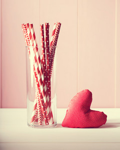 Romantic Valentines Day greeting card design with a handcrafted red heart and glass full of colorful red and white straws against a rustic pink wooden wall