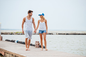 Romantic young beautiful smiling couple walking on the beach holding hands