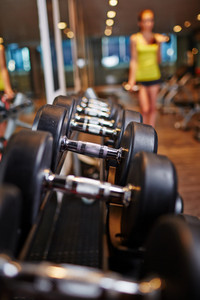 Row of barbells in gym with sporty female standing on background