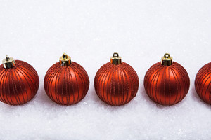Row of red decorative toy balls on the snow
