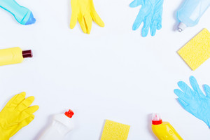 Rubber gloves, sponges and bottles of cleaning fluids on a white background, place for text, top view